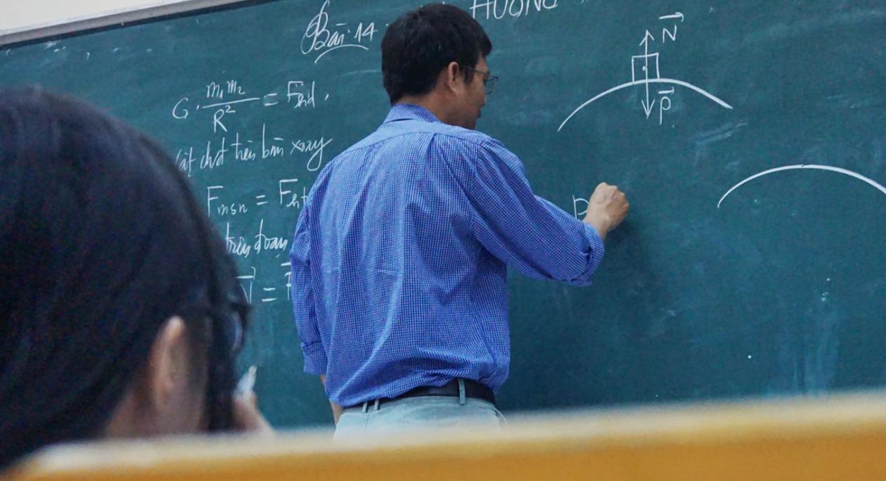 teacher writing on black board